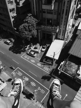 Grayscale Photography Man Wearing All Star Converse High Tops Below in Street and Building #45421