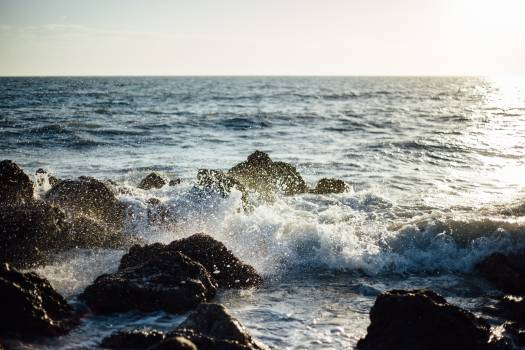 Photo of Blue Ocean Wave Coming to the Rocky Shore Free Photo