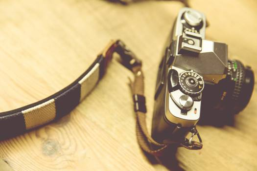 Black Camera With White and Black Strap on Beige Surface #46367