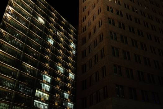 Brown Concrete Building Beside Black Concrete Building during Night Time #46747