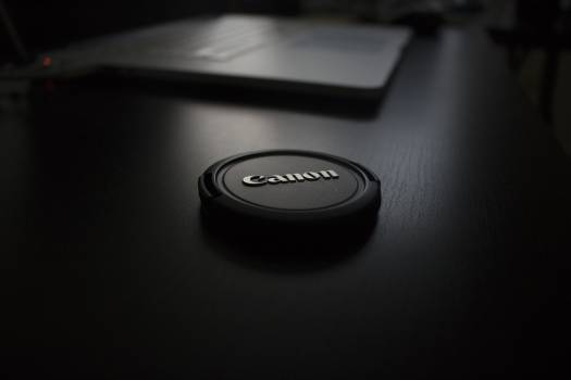 Black Canon Lens Cover on Black Wooden Surface #47599