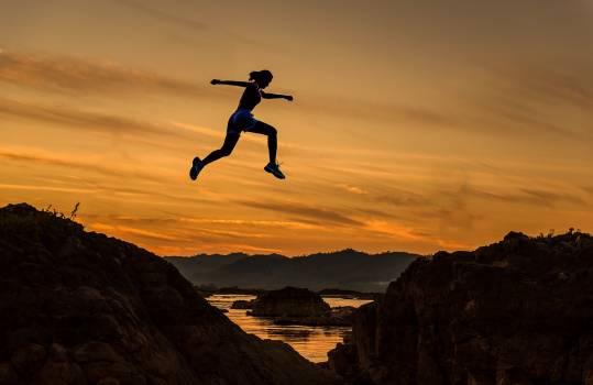 Man Jumping on Landscape at Sunset Free Photo