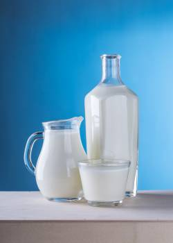 Close-up of Milk Against Blue Background Free Photo