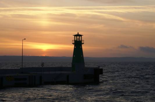 Lighthouse by Sea Against Sky during Sunset Free Photo