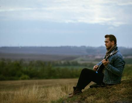 Young Man Playing Guitar on Landscape Against Sky Free Photo
